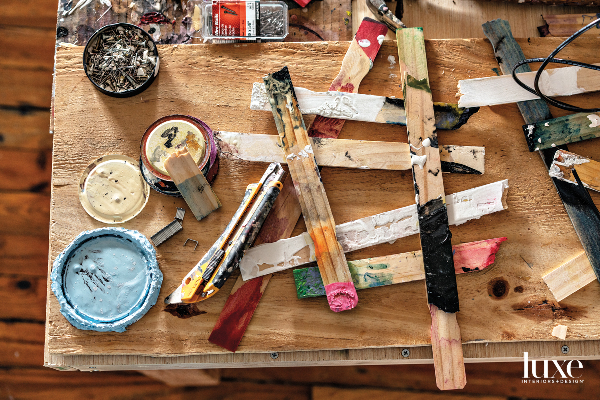 tabletop of paint, brushes and wooden stirrers