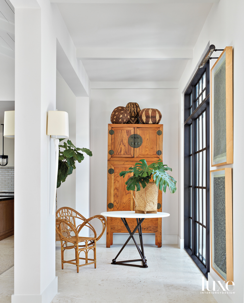 entryway with white walls, table,...
