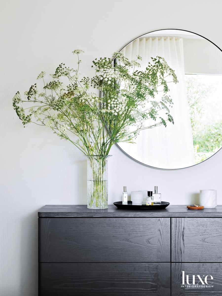 round mirror and floral arrangement...
