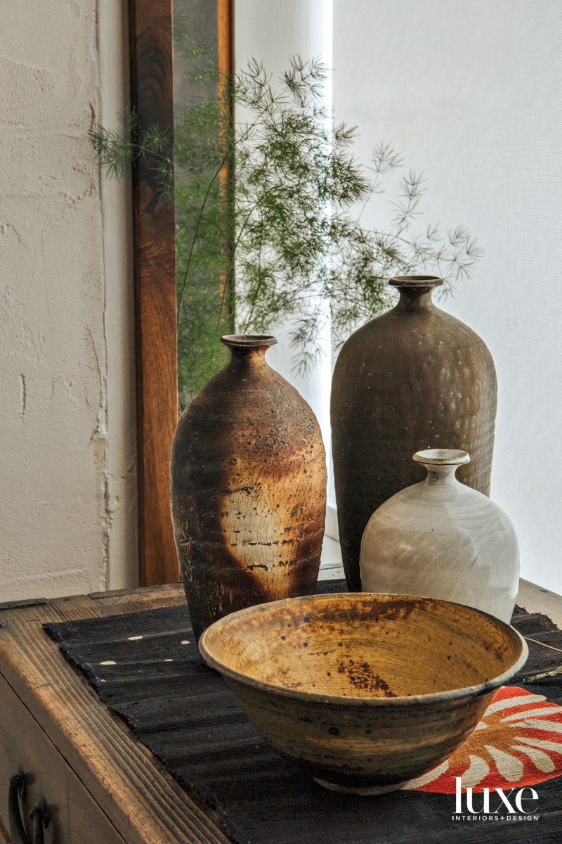 Three vases and a bowl make up a vignette in the gallery window.
