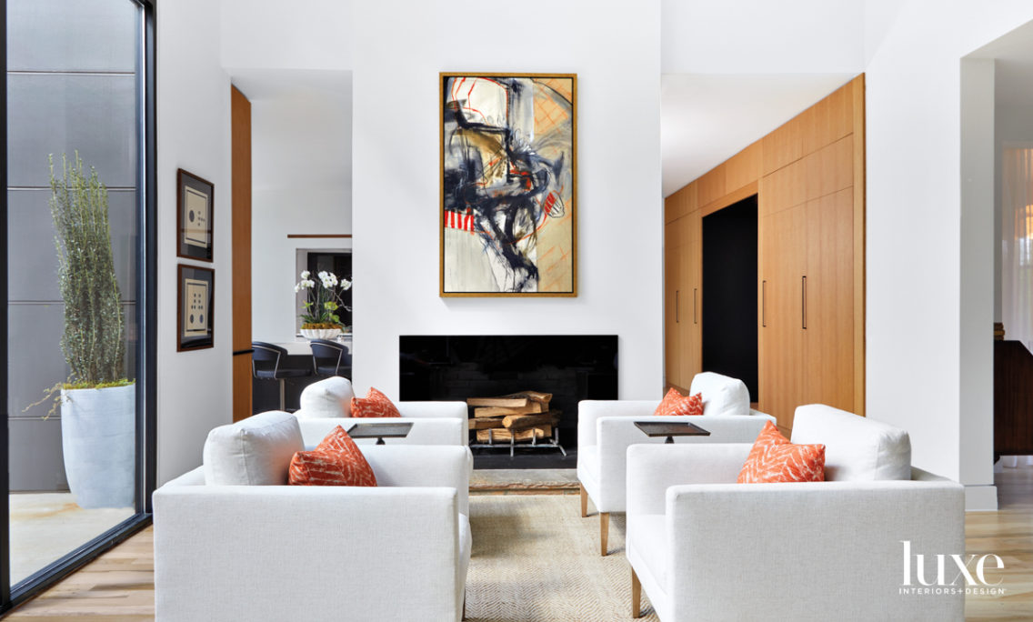 Living room with four club chairs, orange pillows, abstract artwork and white oak cabinetry