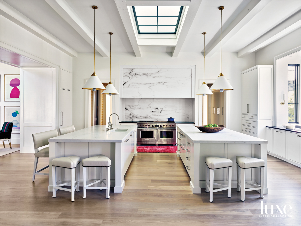 Open-format kitchen with skylight, a pair of islands, double ovens and four contemporary ceiling pendants