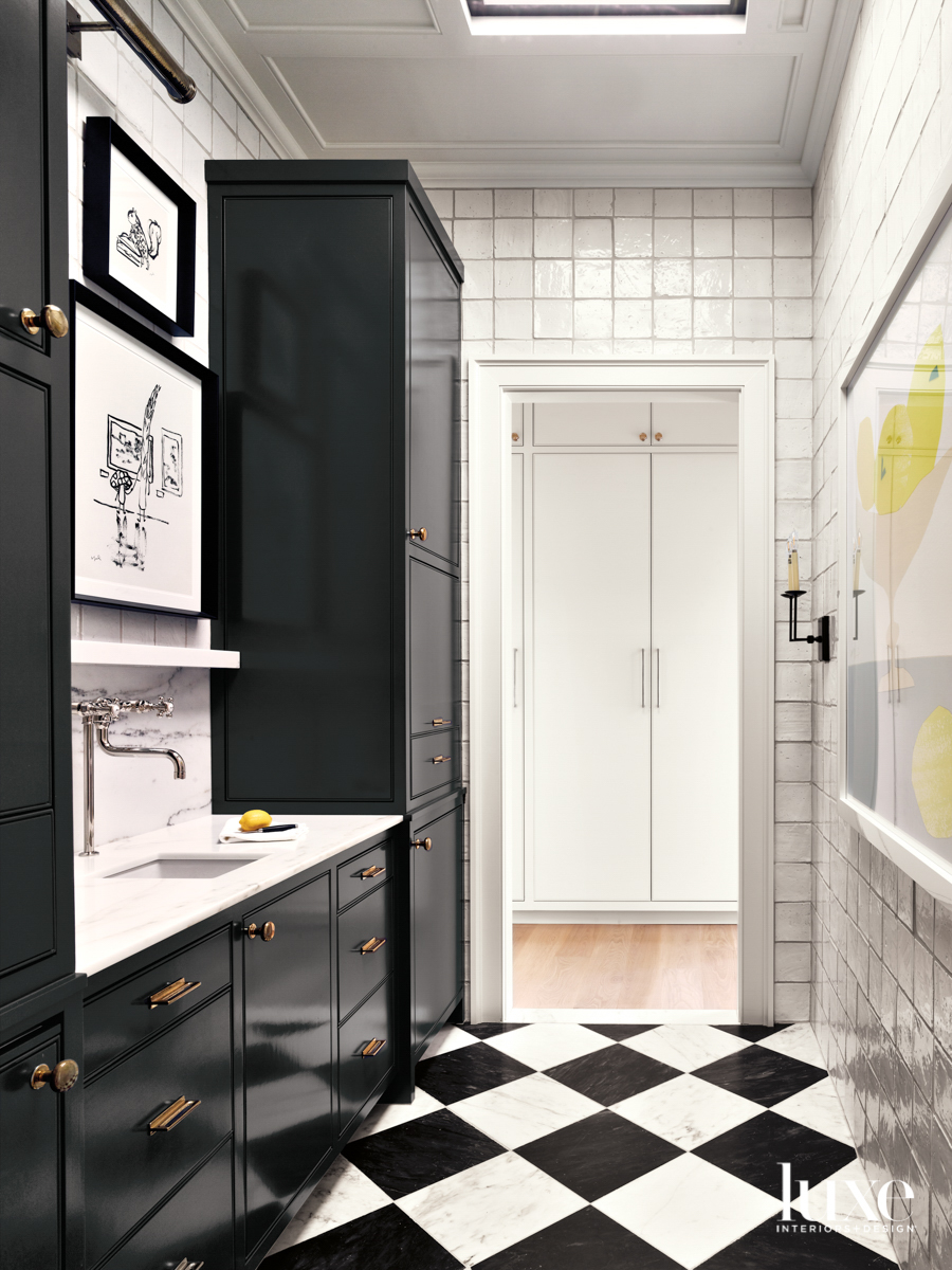 Pantry with charcoal cabinetry, black-and-white checkerboard floors and white-tiled walls