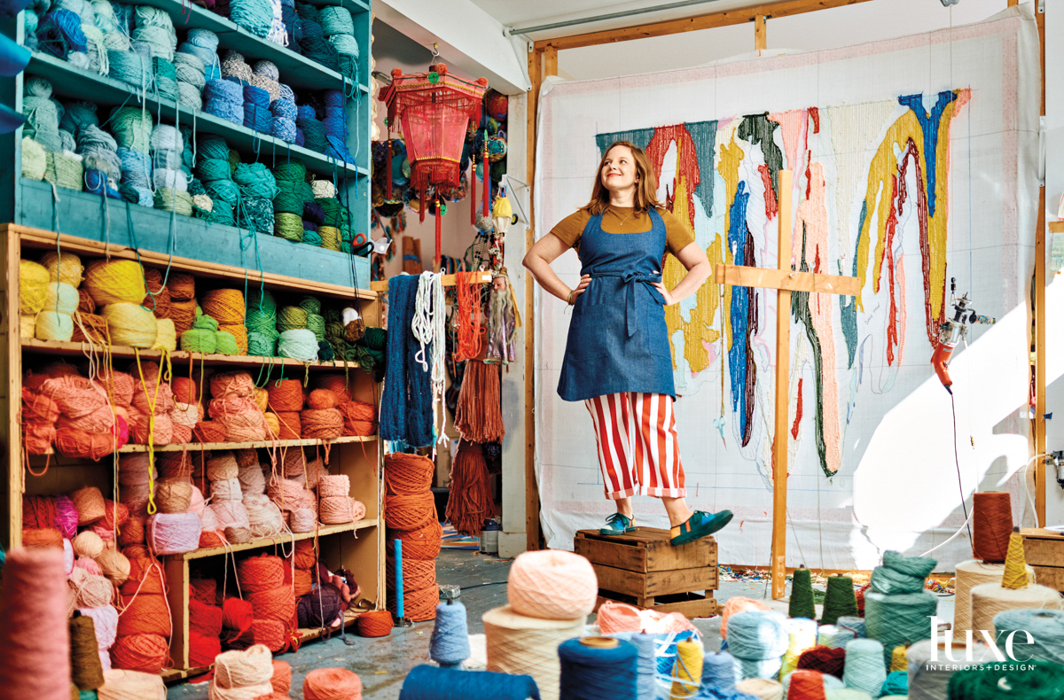 Woman wearing red striped pants and a denim apron standing in artist studio surrounded by hundreds of spools of colorful yarn