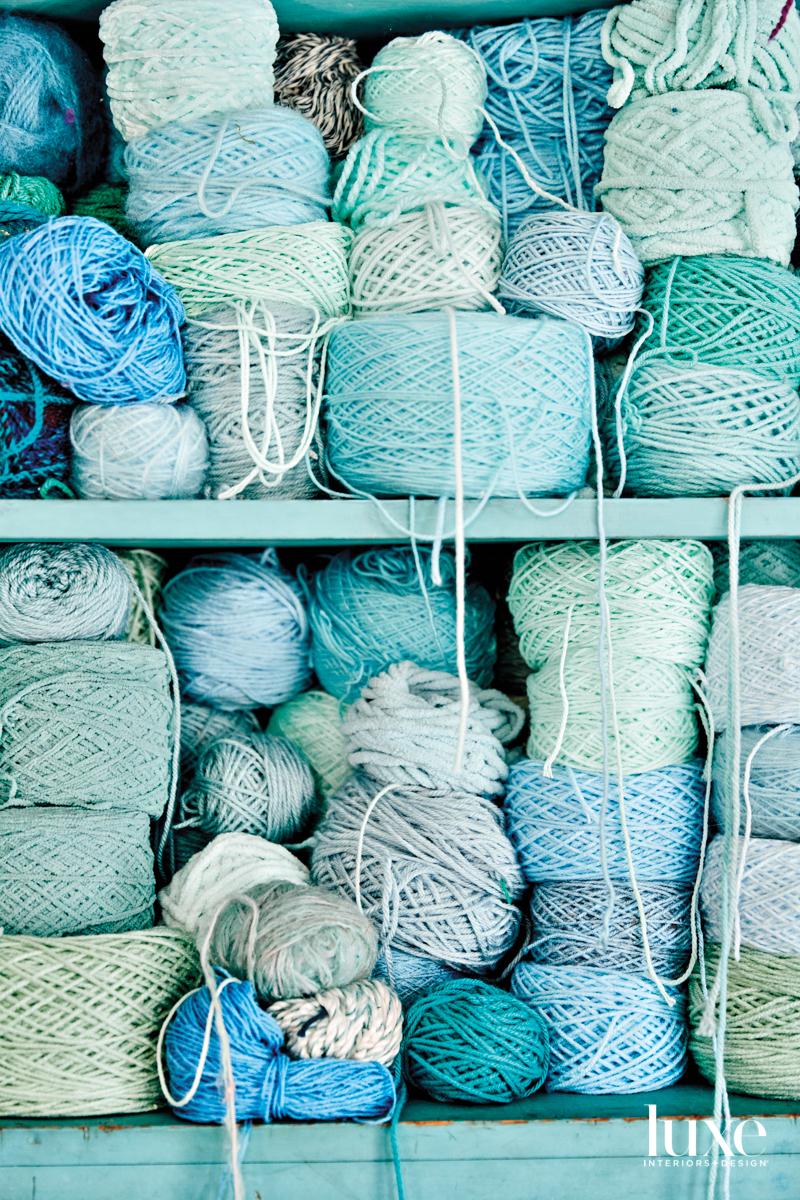 An aqua bookshelf overflowing with spools of yarn in varying shades of aqua