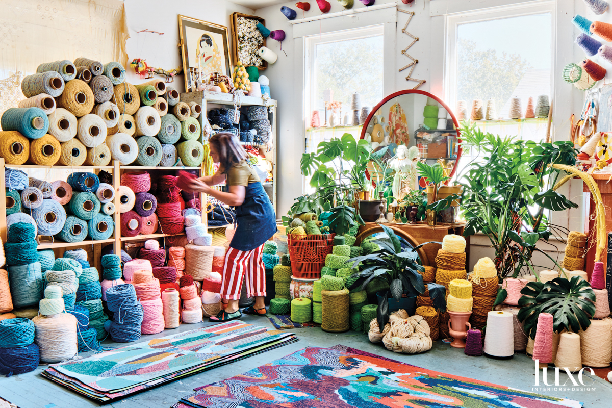 Spacious artist studio filled with colorful floor mats and shelves stacked with colorful spools of yarn
