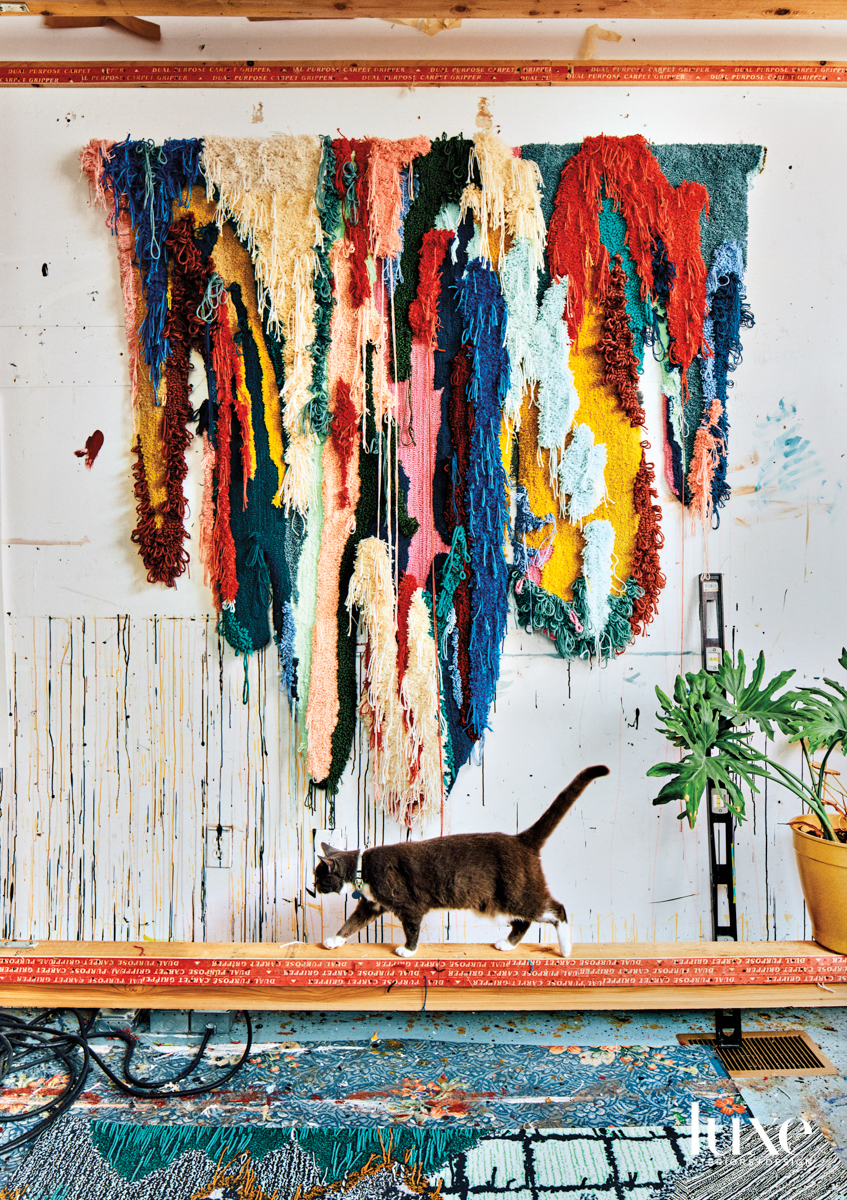 Multicolored, textural wall hanging above a bench with a strolling cat