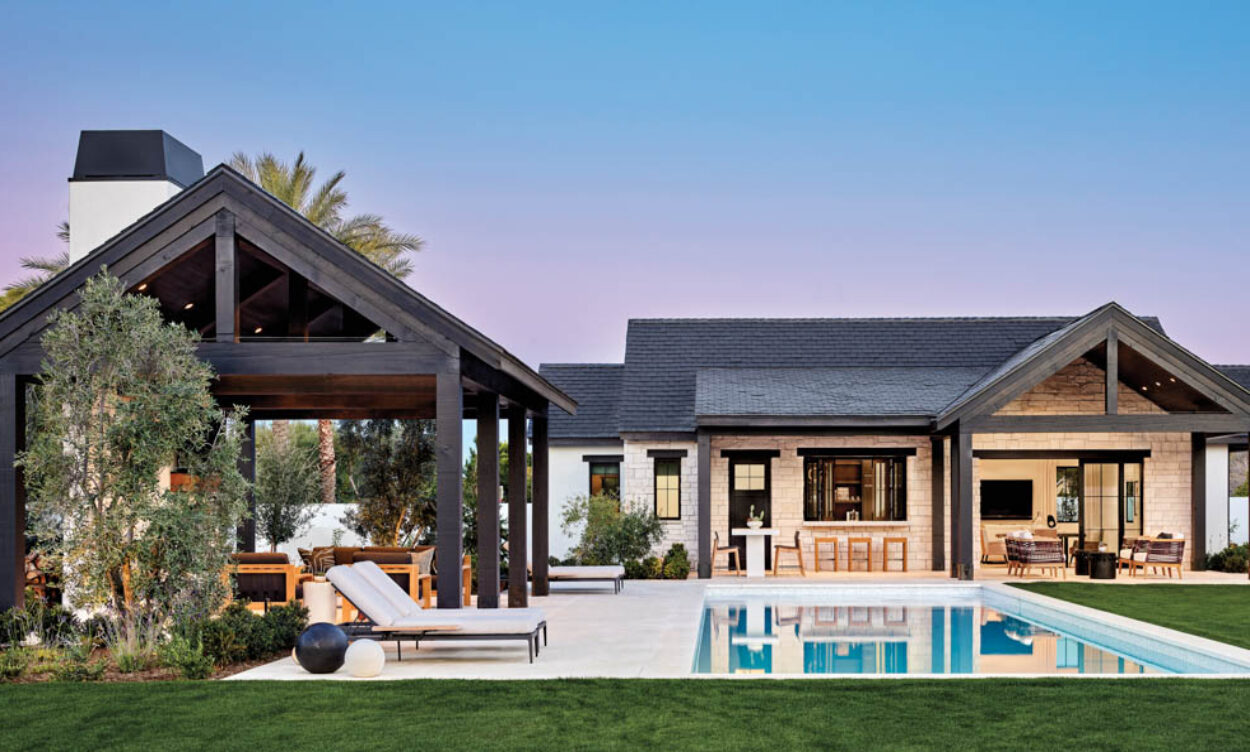 The backyard of a home with a pool at twilight.