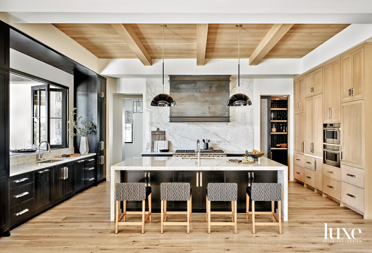 A kitchen with dark cabinetry,...