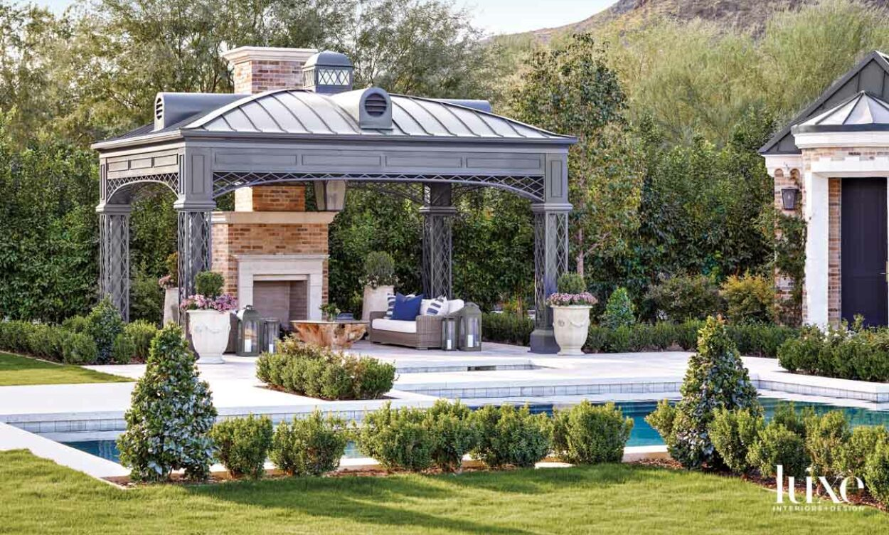 A fireplace pavilion with seating that sits next to the pool. You see mountains in the background.