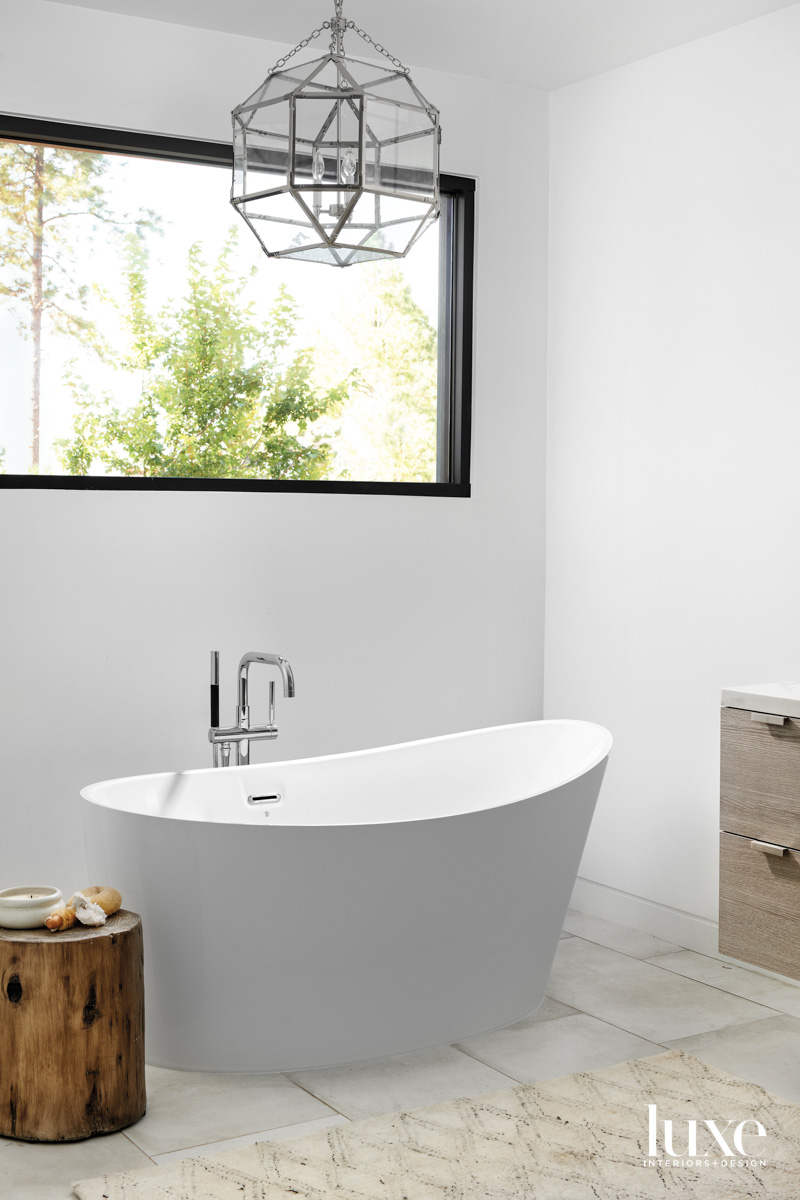 A white standalone bathtub with...