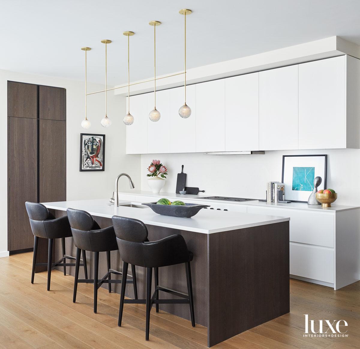white kitchen with brown island...