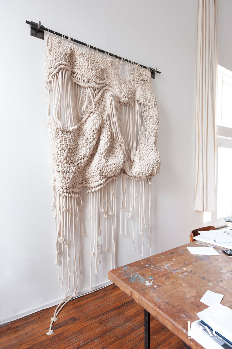 A rope weaving hanging on a white wall.