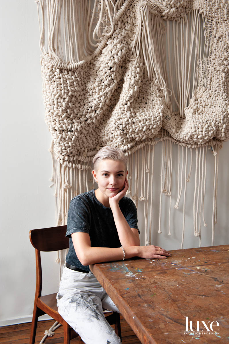 A woman with short hair since at a table in front of a rope hanging.