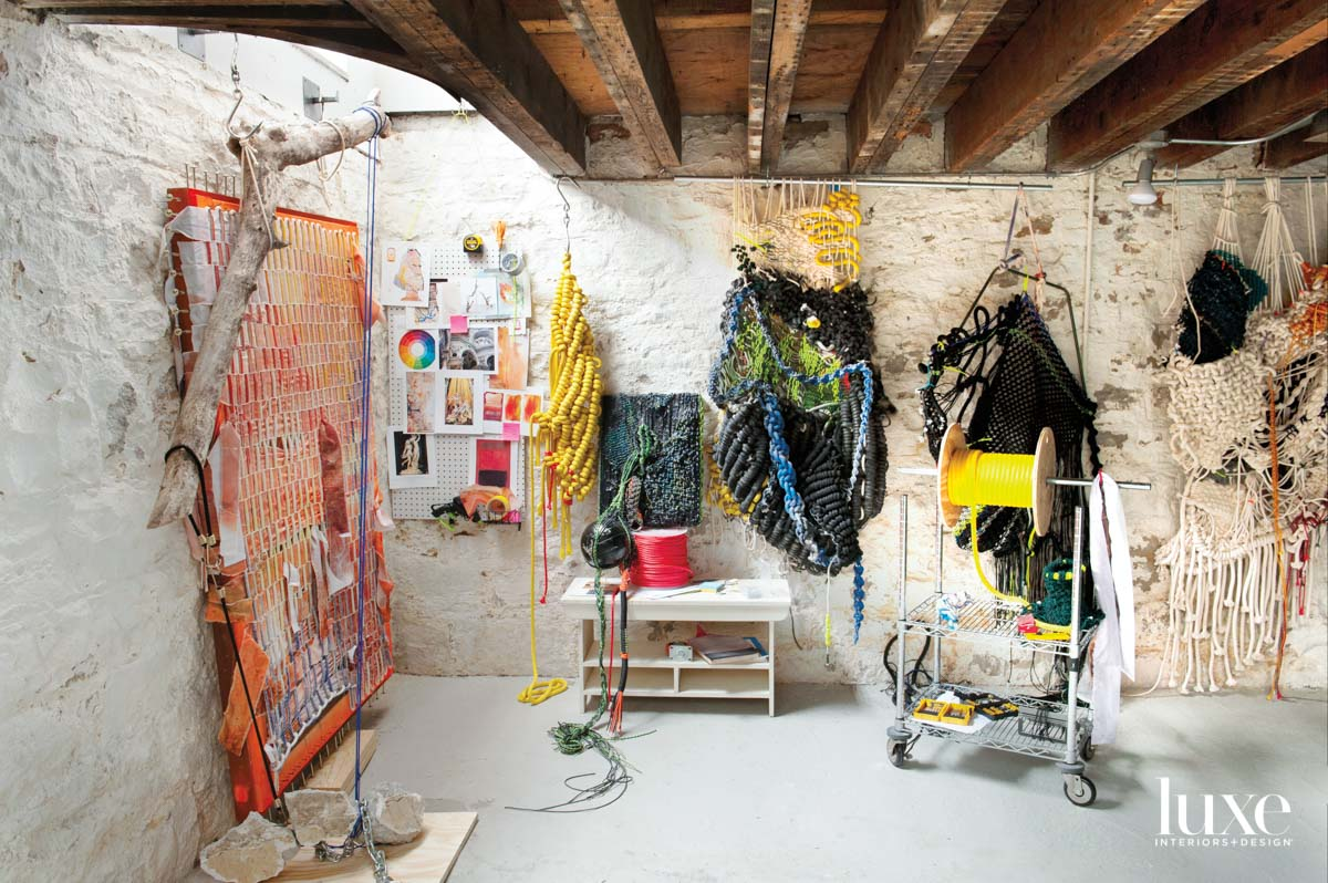 Sculptures made from various colors of rope hang in a room with wooden ceiling beams.