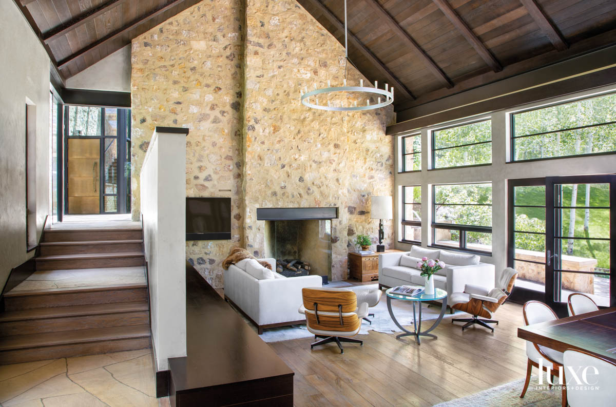 A living room has a high ceiling and stone fireplace.