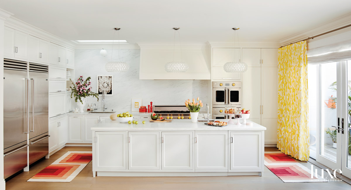 A white kitchen has colorful...