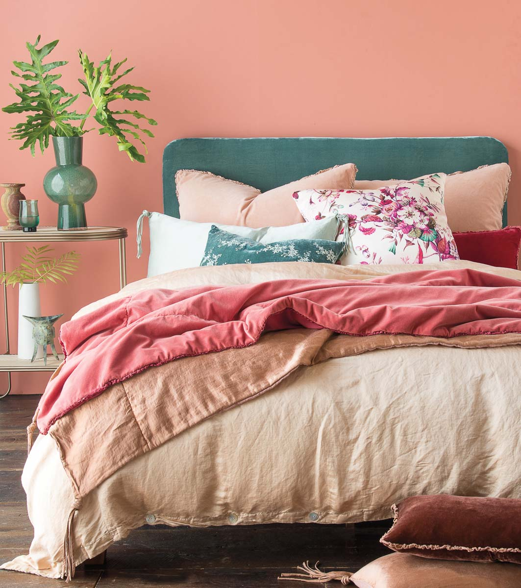 Bed with green headboard and pink and neutral linens