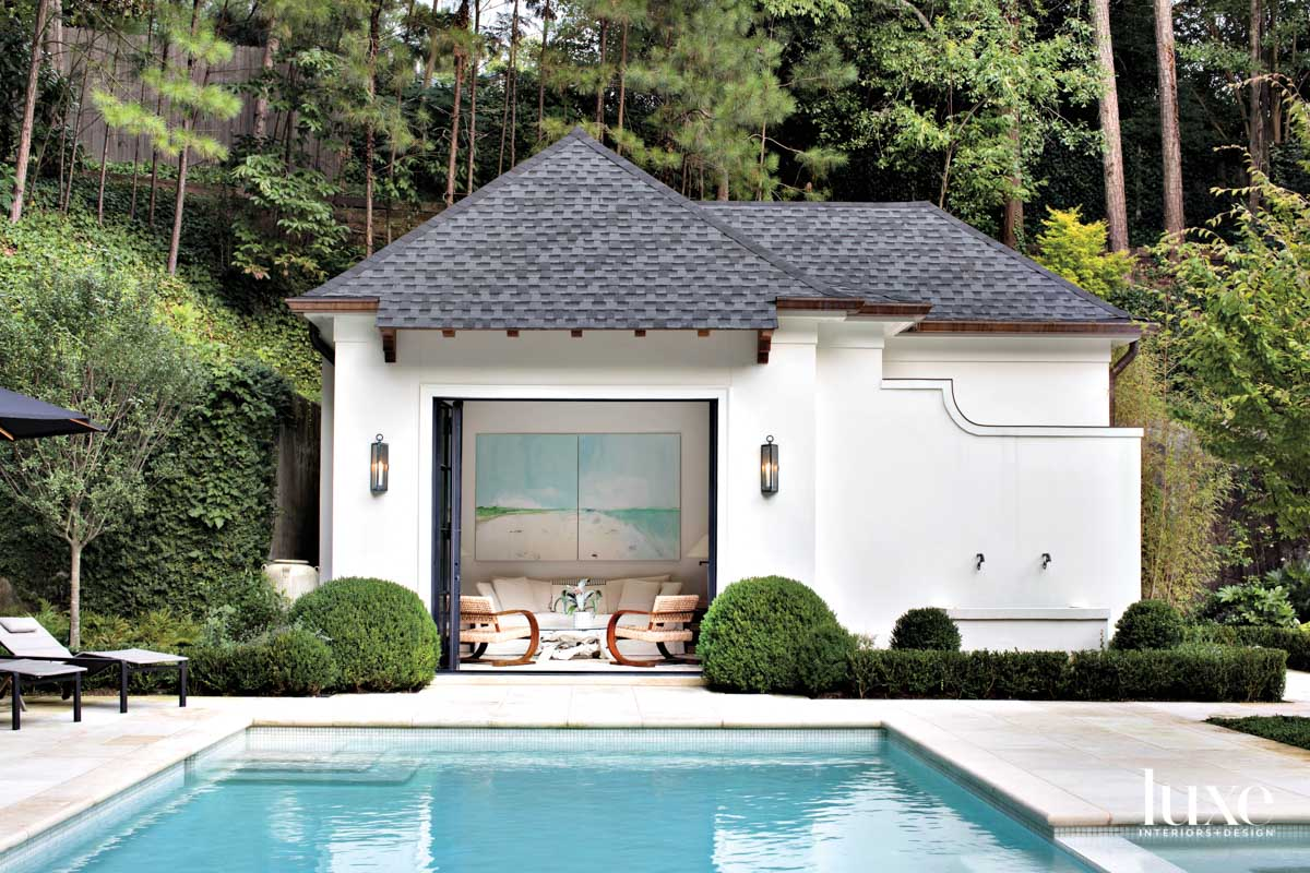 Stucco pool house with open...