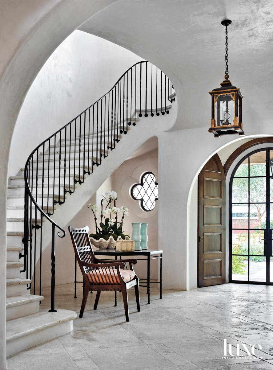 Entryway with plaster walls, curving staircase and quatrefoil-shaped window