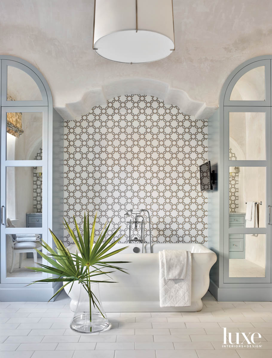 Spacious bathroom with built-in mirrored cabinets, plaster walls, a tile accent wall and standalone soaking tub