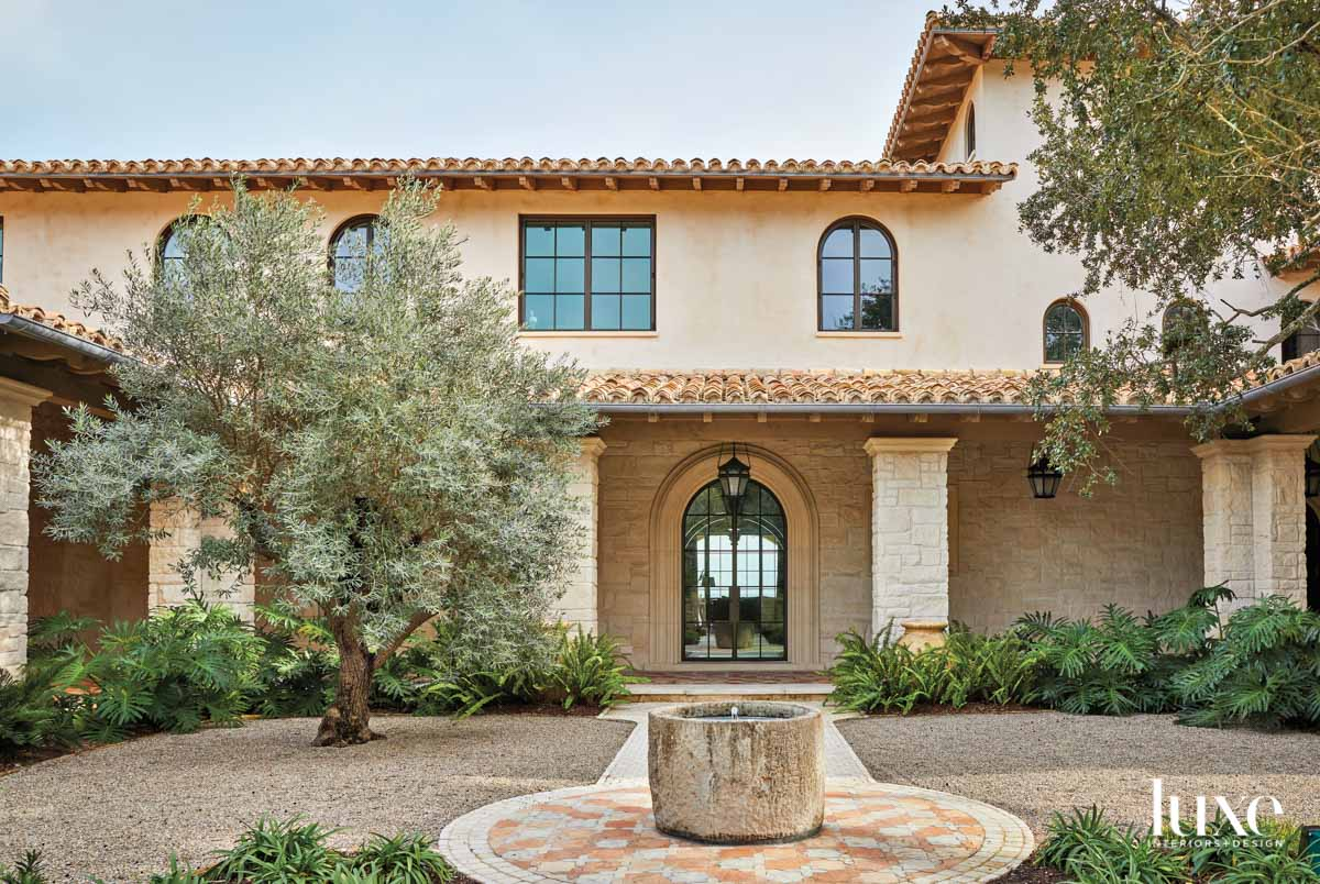 Spanish-inspired villa with tile roof,...