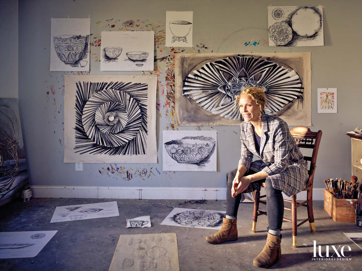 Seated woman in front of a wall with artwork taped to it