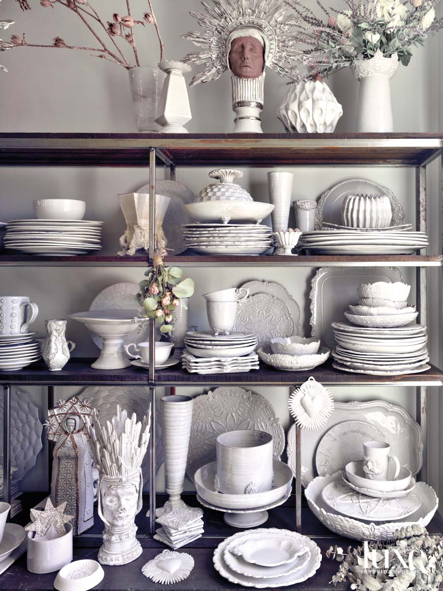 Shelves stacked with white dinnerware and ceramics