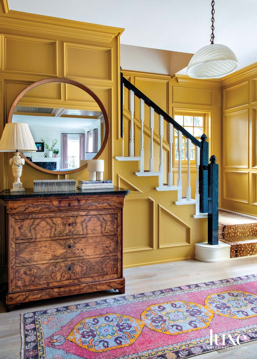 Foyer with antiques and yellow-painted paneling