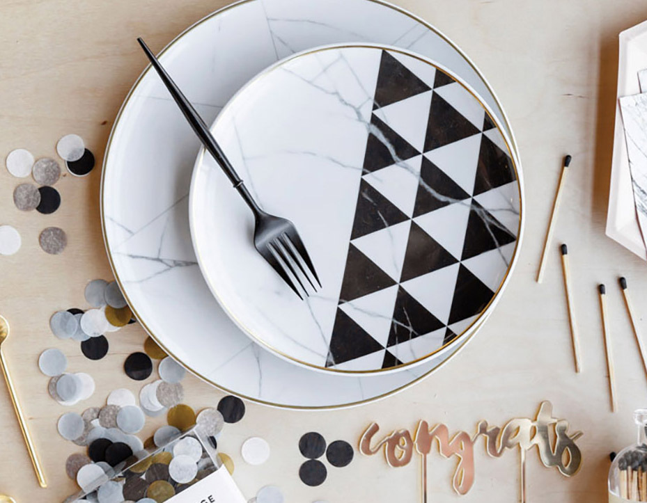 Tablescape including plate with black and white triangle pattern and confetti.