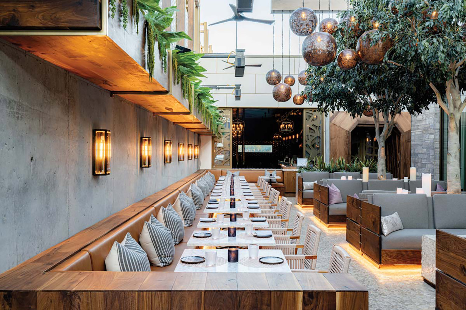 Outdoor seating area at restaurant with wood accents and greenery