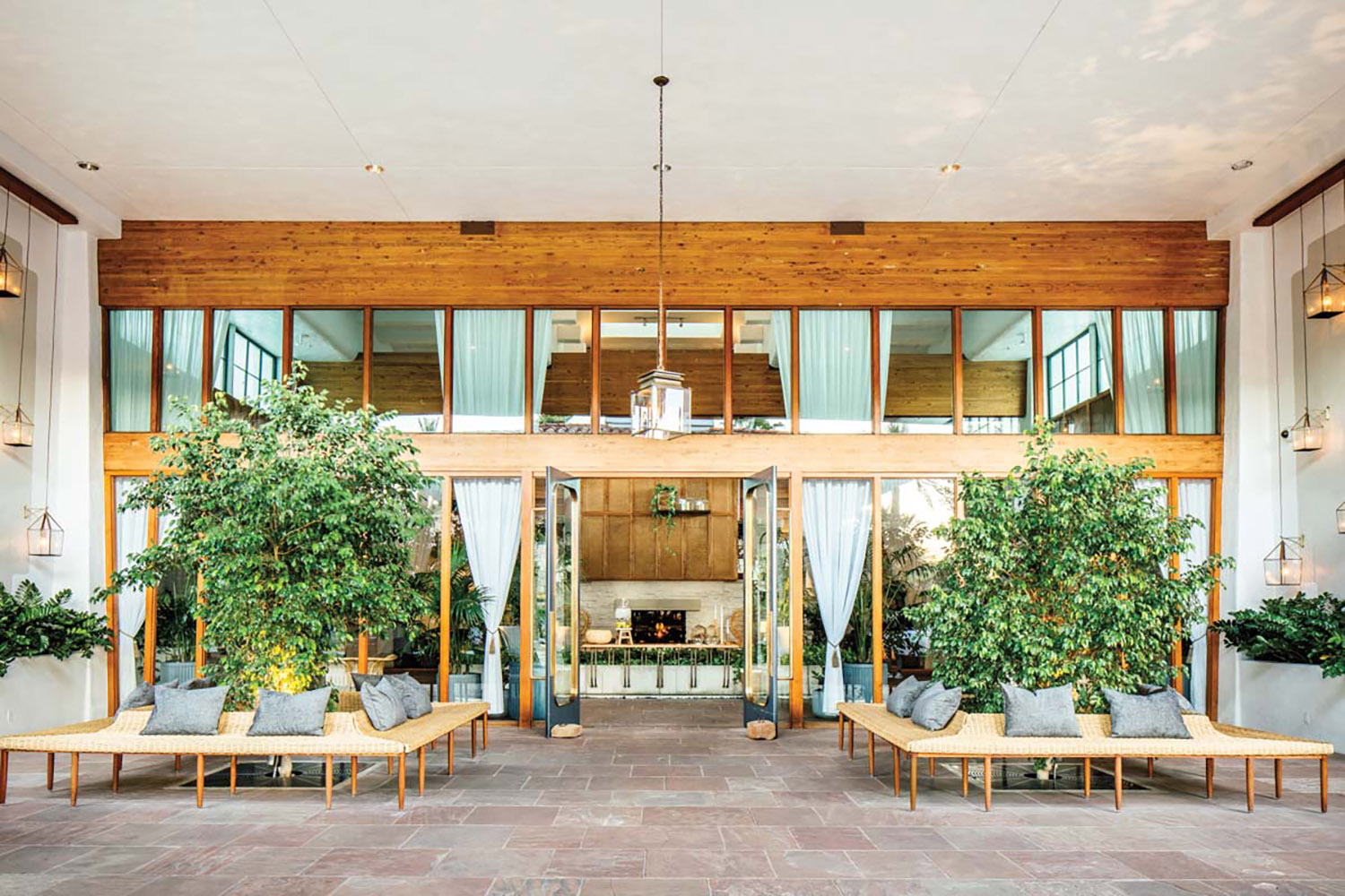 Resort entrance with wood accents, large windows and greenery.