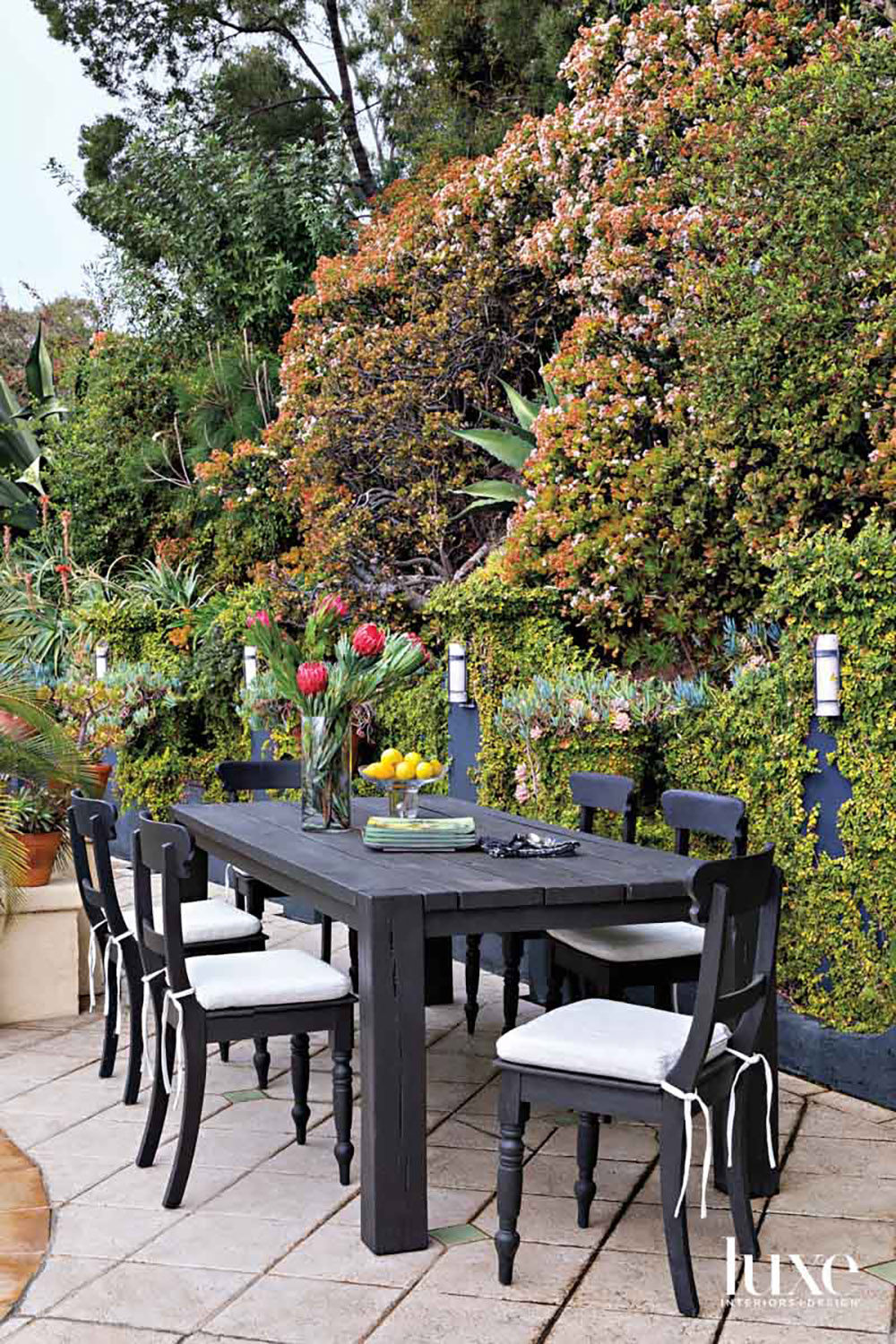 Patio furnished with black dining...