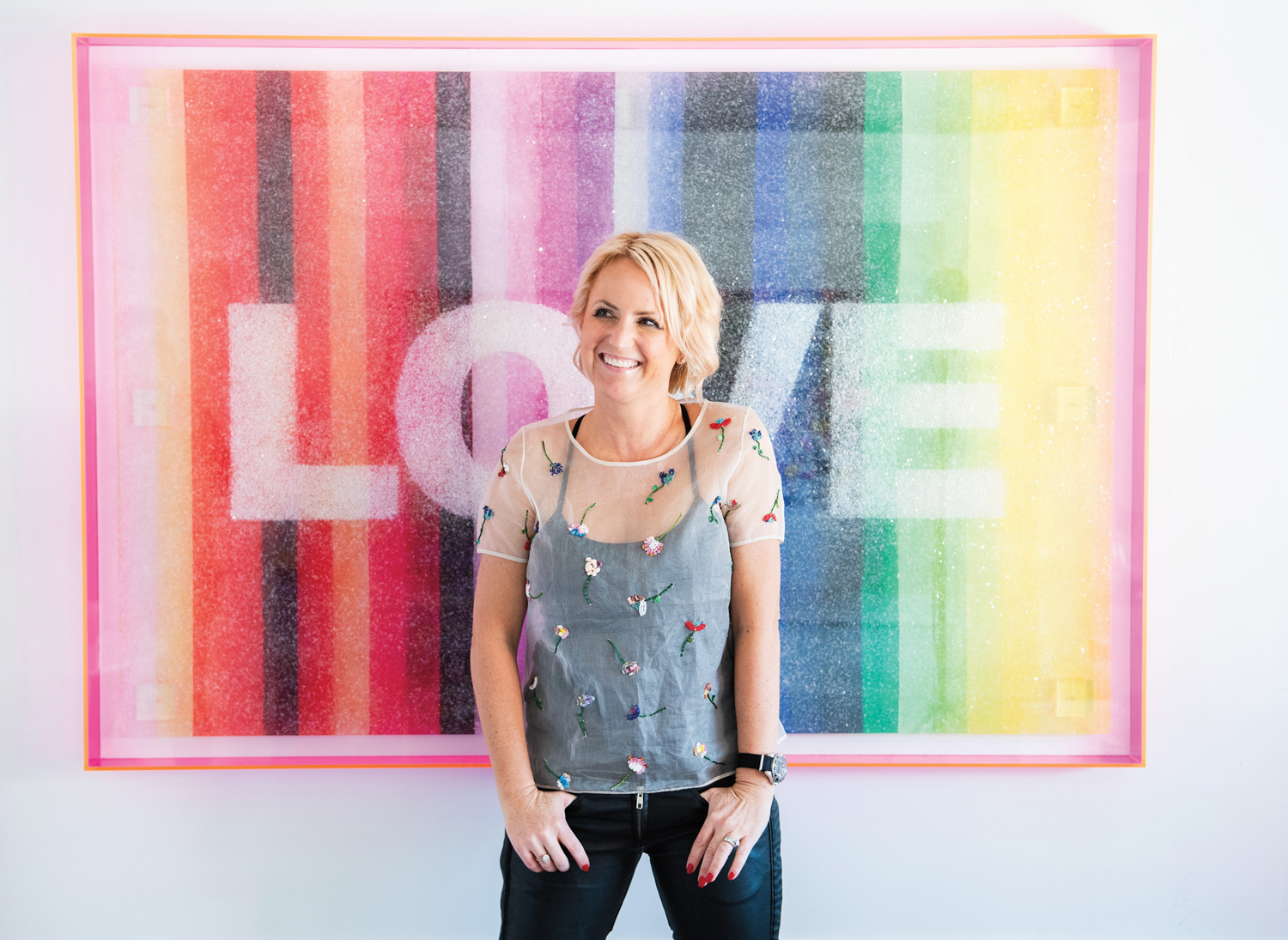 Artist in front of rainbow-colored artwork
