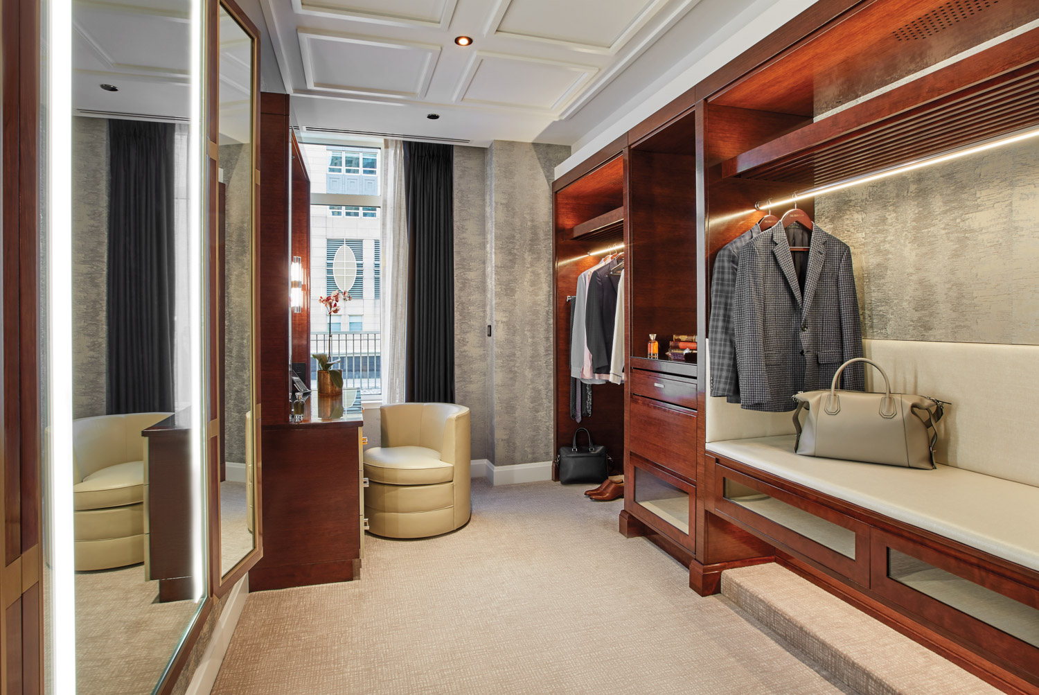 Walk-in closet in hotel suite with wood shelving