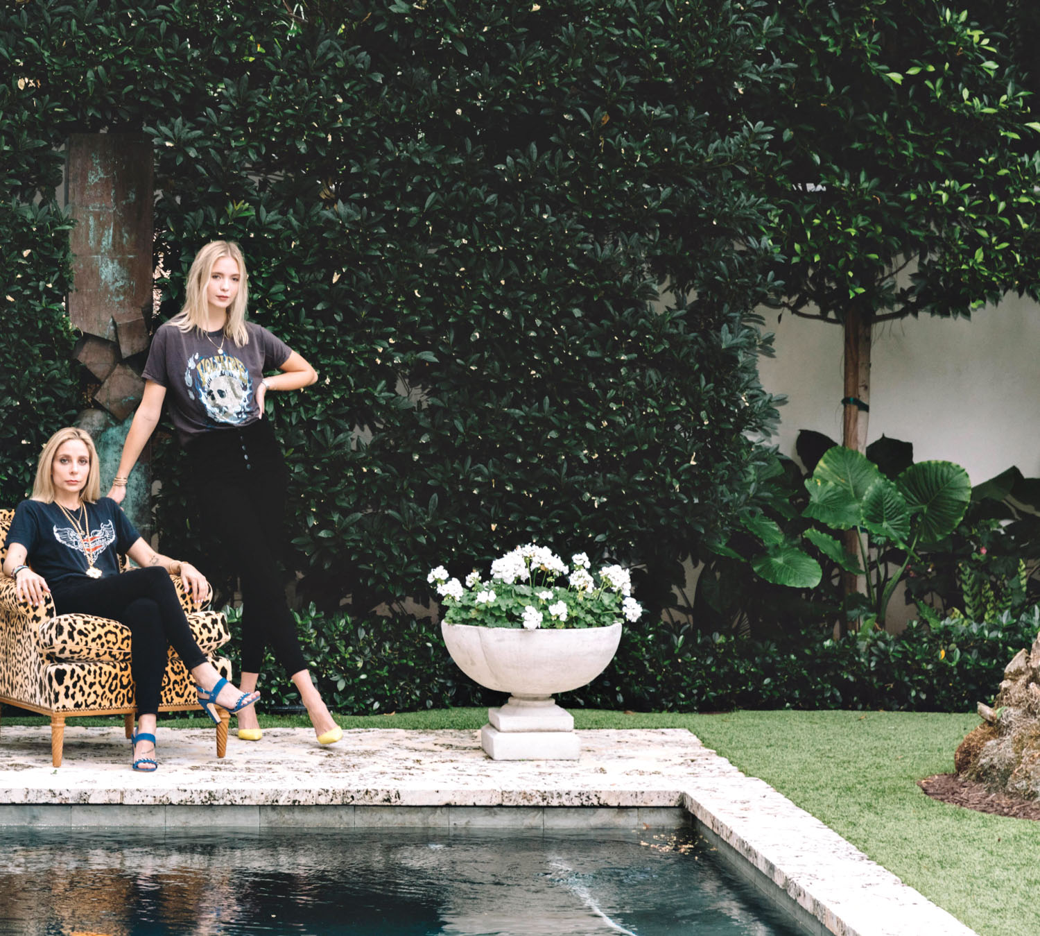 Portrait of two designers in a garden by a pool
