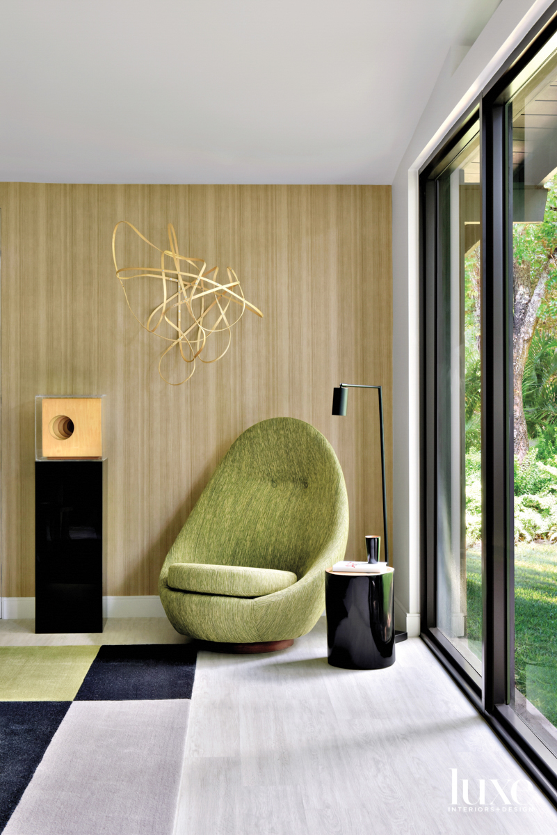 green chair against wood-patterned wallcovering...