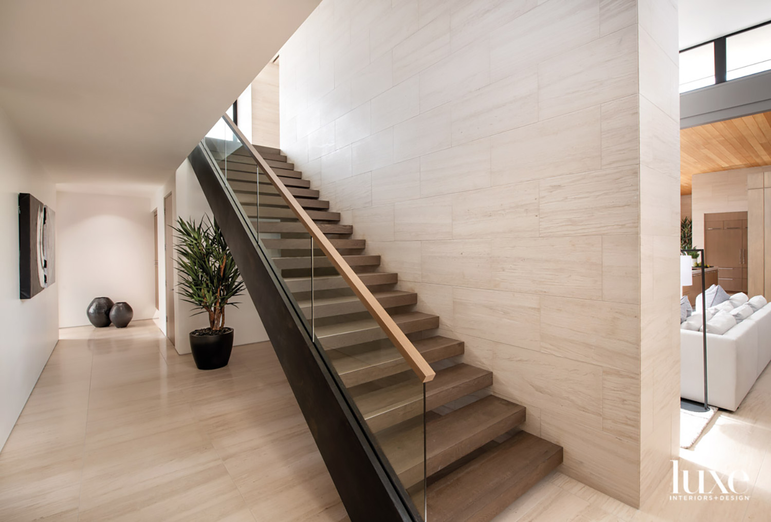 A glass-steel-and-wood staircase leads to...