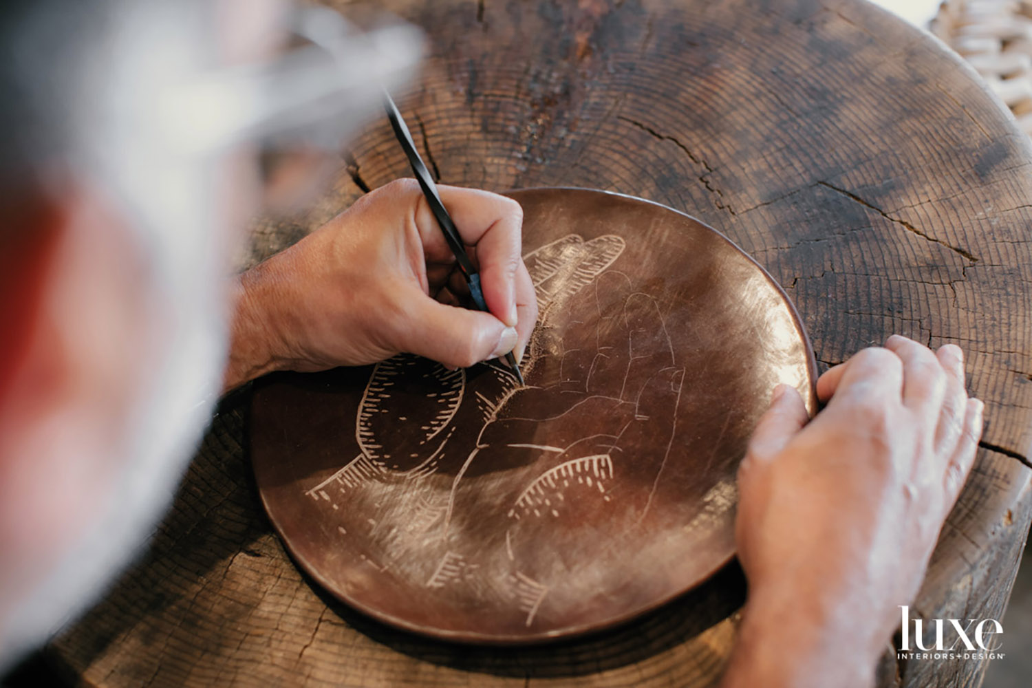 A hand etching a plate