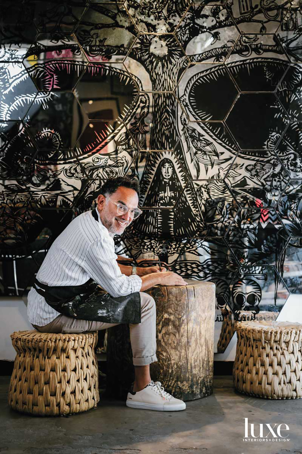 A man sitting on a stool smiling at the camera. Behind him is artwork.