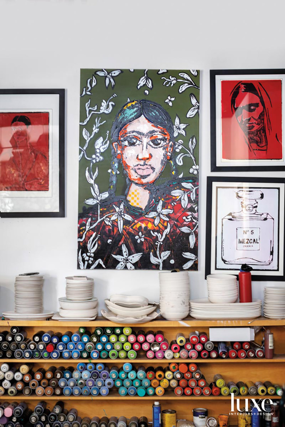 A group of paintings above shelves with ceramics and paint