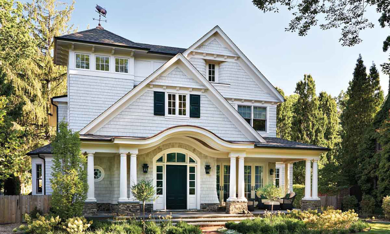 The exterior of a gray Shingle-style house.