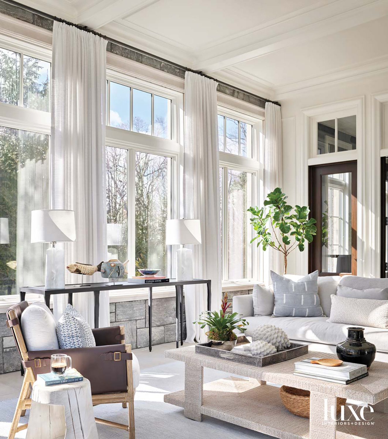 A sunroom with a light gray sofa, a brown leather chair and a textured coffee table.