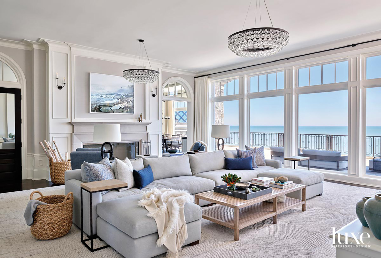 gray living room with large sectional, a fireplace and two chandeliers. The room has floor-to-ceiling windows