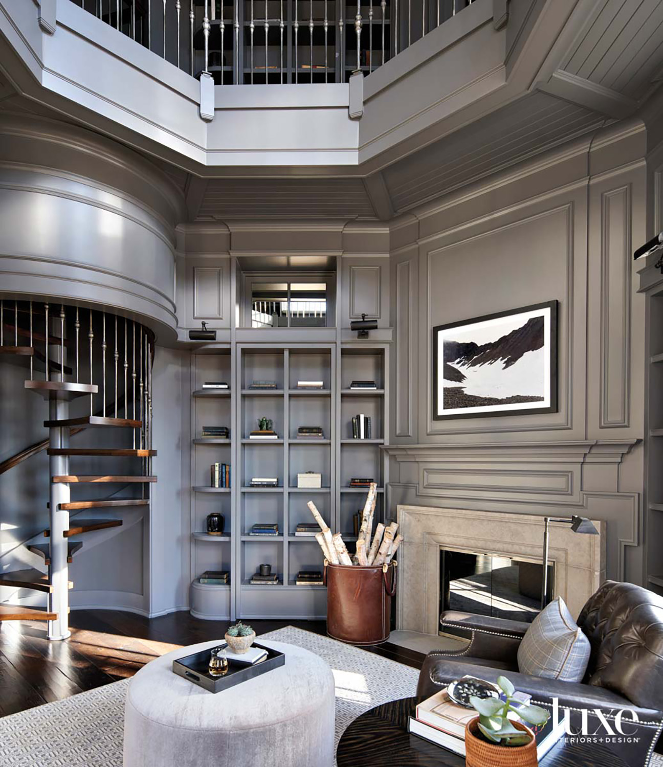 A gray double-height home library with a fireplace and a large leather chair next to a light gray ottoman.
