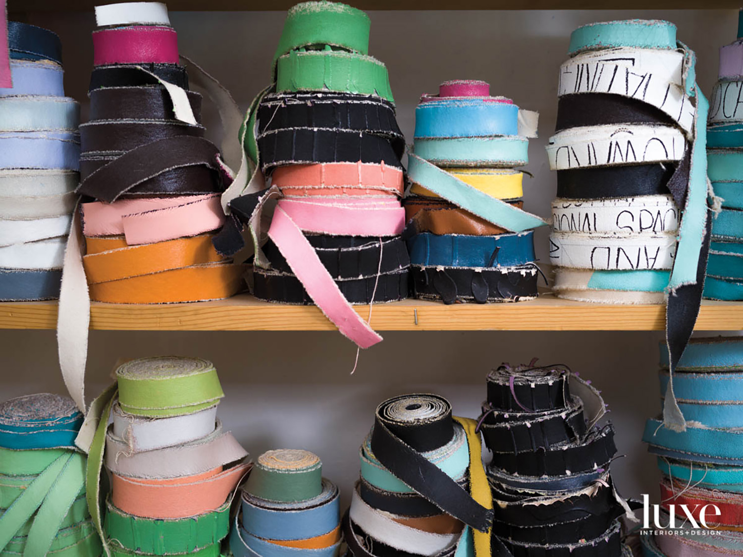 Shelves with spools of colored canvas strips.
