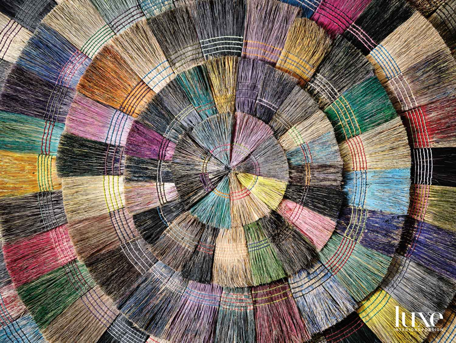 Painted brooms are composed into artwork.