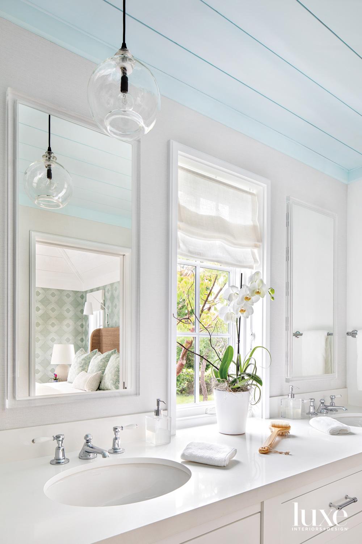 white bathroom with glass pendant...