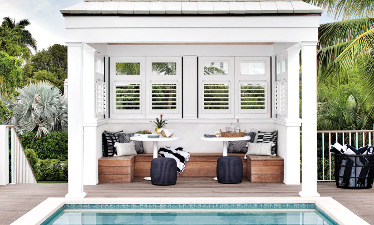 pool deck with white cabana outfitted with bench, white tables and black ottomans