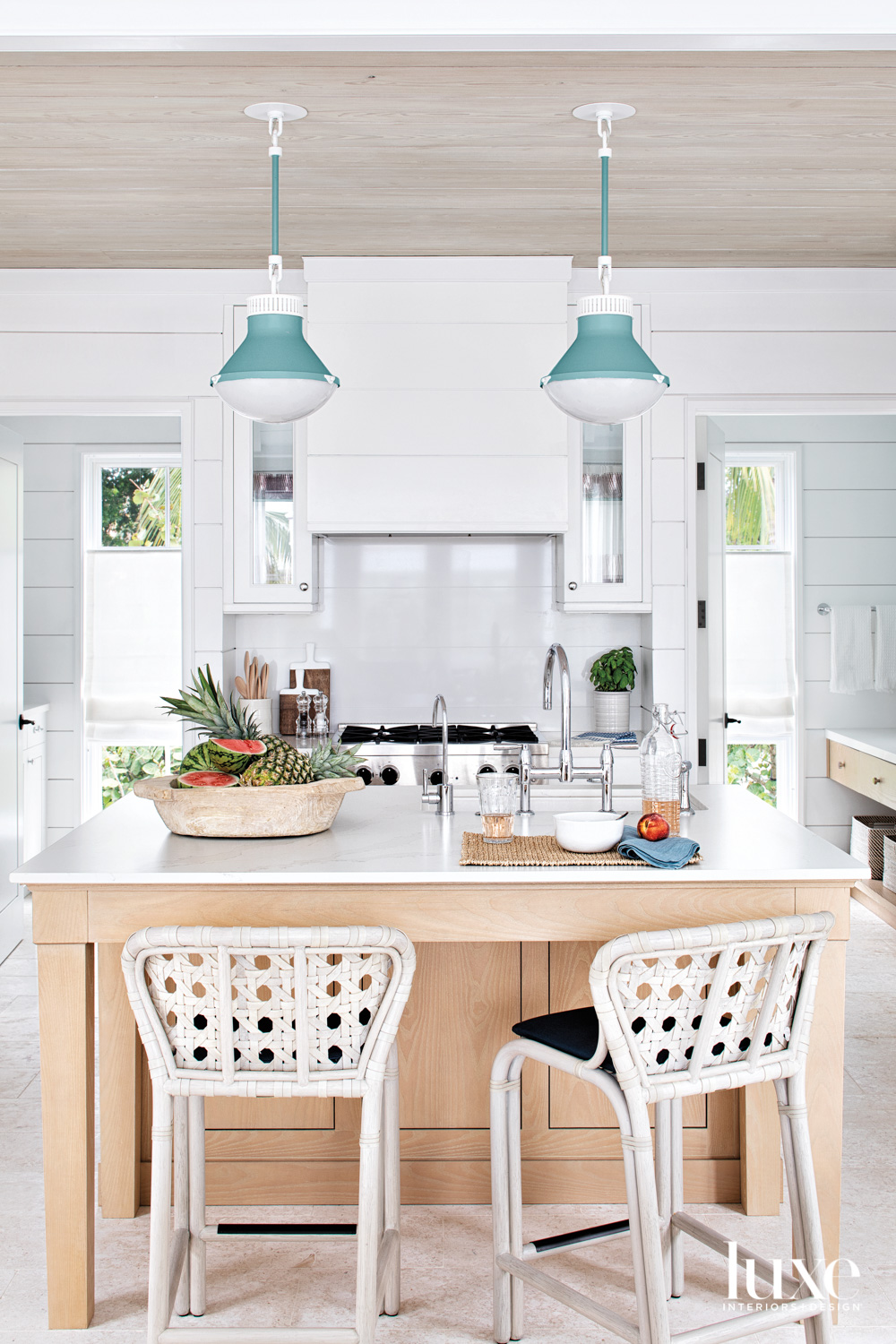 kitchen with teal pendants, white...